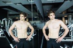 Exercício 'sexy' muscular novo do homem no gym perto das sombras do espelho Fotos de Stock