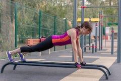 Exercícios caucasianos novos da mulher na terra de esportes do parque Em uma posição da prancha dos esportes, sportswear brilhant fotografia de stock