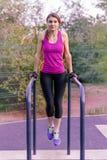 Exercícios caucasianos novos da mulher na terra de esportes do parque Levantando na barra horizontal, sportswear brilhante Fones  imagens de stock royalty free