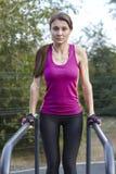 Exercícios caucasianos novos da mulher na terra de esportes do parque Levantando na barra horizontal, sportswear brilhante Fones  imagem de stock