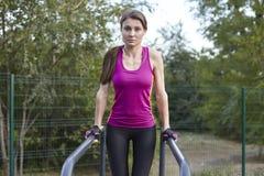 Exercícios caucasianos novos da mulher na terra de esportes do parque Levantando na barra horizontal, sportswear brilhante Fones  imagens de stock