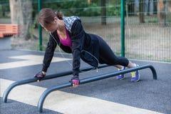 Exercícios caucasianos novos da mulher na terra de esportes do parque A menina em uma posição da prancha dos esportes, sportswear imagem de stock