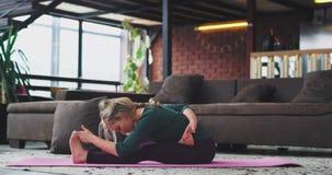 Exercícios duros da ioga na jovem senhora atrativa da manhã que pratica a esticar o corpo, para a energia e para uma saúde filme