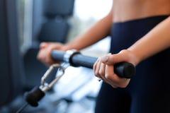 Exercícios no simulador do bloco Extensão do bíceps Exercício atlético da mulher no gym foto de stock royalty free