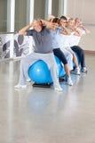 Exercícios traseiros na esfera da ginástica na ginástica Imagem de Stock Royalty Free