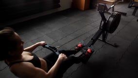 Exerc?cio novo do atleta f?mea com o simulador do poder no movimento lento no gym video estoque