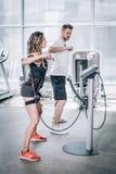 Exerc?cios das mulheres da estimula??o do EMS eletro com o treinador no gym moderno imagens de stock