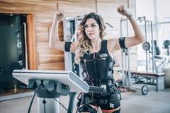 Exerc?cios das mulheres da estimula??o do EMS eletro com o treinador no gym moderno fotos de stock royalty free