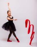 Exercício louro novo bonito do calilisthenics do treinamento da ginasta do bailado da mulher com a fita vermelha com sapatas verm Imagens de Stock