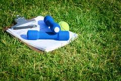 Exercez l'équipement, la balle de tennis, et le presse-papiers sur l'herbe Image libre de droits