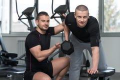 Exercice arrière de Helping Man On d'entraîneur personnel image stock