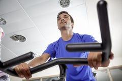 Exercice avec des bicyclettes dans un gymnase Photographie stock