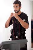 Exercice convenable d'homme sur l'électro machine musculaire de stimulation Photos stock