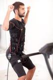 Exercice convenable d'homme sur l'électro machine musculaire de stimulation Images stock