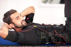 Exercice convenable d'homme sur l'électro machine musculaire de stimulation Photographie stock libre de droits
