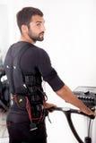 Exercice convenable d'homme sur l'électro machine musculaire de stimulation Photographie stock