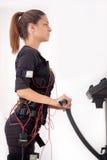 Exercice convenable de femme de jeunes sur l'électro machine musculaire de stimulation Images stock
