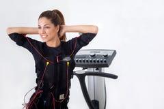 Exercice convenable de femme de jeunes sur l'électro machine musculaire de stimulation Photographie stock libre de droits