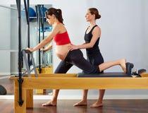 Exercice de Cadillac de réformateur de pilates de femme enceinte photo stock
