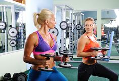 Exercice de deux bel femmes en gymnastique avec des poids photographie stock