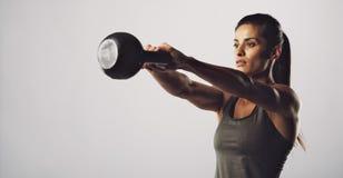 Exercice de femme avec la cloche de bouilloire - séance d'entraînement de Crossfit Photographie stock libre de droits