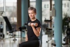 Exercice de jeune femme avec des haltères Photographie stock libre de droits