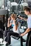Exercice de jeune femme de centre de forme physique avec l'avion-école Image stock
