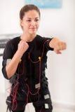Exercice de jeune femme sur l'électro machine de stimulation Photo stock