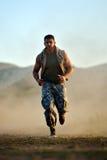 Exercice de jeune homme extérieur sur le champ poussiéreux Photographie stock