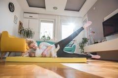 Exercice de mère avec son bébé à la maison photographie stock libre de droits