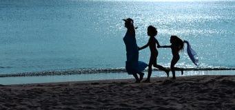 Exercice de matin - femme et enfants courant sur la plage Images stock