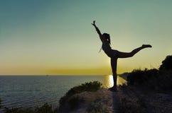 Exercice de silhouette de fille gymnastique au coucher du soleil Images stock