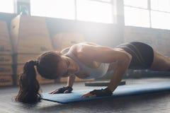 Exercice femelle sur le tapis de forme physique au gymnase Photographie stock