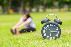 Exercice pendant le matin et l'horloge noire Images stock
