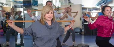 Exercice plus âgé avec les bâtons gymnastiques dans le gymnase moderne Photo libre de droits