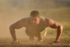 Exercice sportif de jeune homme extérieur sur le champ poussiéreux Photo libre de droits