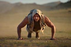 Exercice sportif de jeune homme extérieur sur le champ poussiéreux Images libres de droits