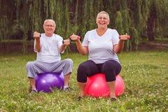 Exercice supérieur - couple de retraité tenant des haltères tout en se reposant sur la boule de forme physique en parc photos stock