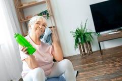Exercice supérieur de femme à la maison se reposant sur le rafraîchissement de boule d'exercice photo libre de droits