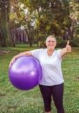 Exercice supérieur - pouce pour la femme de exercice en bonne santé avec des boules de forme physique en parc images libres de droits