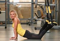 Exercices d'entraînement de la forme physique TRX à la femme de gymnase photo stock