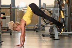 Exercices d'entraînement de la forme physique TRX à la femme de gymnase photos libres de droits