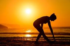 Exercices de corps sur la plage au coucher du soleil Images stock
