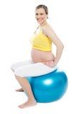 Exercices de femme enceinte avec la bille gymnastique photo libre de droits