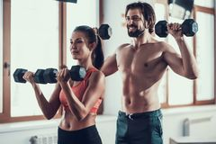 Exercices de fille et de Guy In Gym Doing Dumbbells image stock