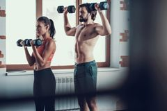 Exercices de fille et de Guy In Gym Doing Dumbbells images stock
