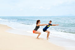 Exercices de forme physique Couples sains s'accroupissant, s'exerçant sur la plage Photo libre de droits