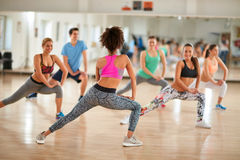 Exercices femelles d'exposition d'instructeur au groupe de forme physique Photos stock