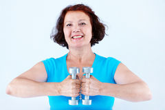Exercise. Portrait of middle-aged female doing physical exercise with dumbbells Stock Image