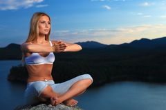 Exercise. Slender young woman doing yoga exercise outdoors royalty free stock photography